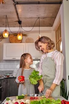 Красивая взрослая мама и дочь собираются вместе приготовить свежий салат с овощами. еда, концепция семьи