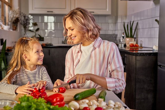 Beautiful adult mother and daughter are going to prepare fresh salad together, having vegetables. food, family concept