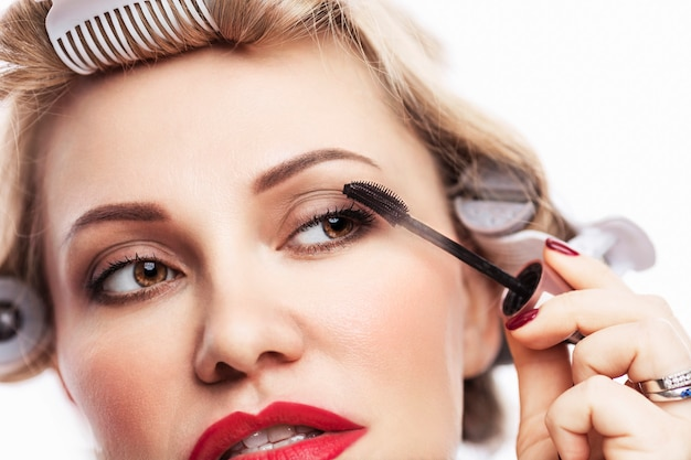 Beautiful adult woman blonde in curlers paints eyelashes with mascara. white background. close-up.