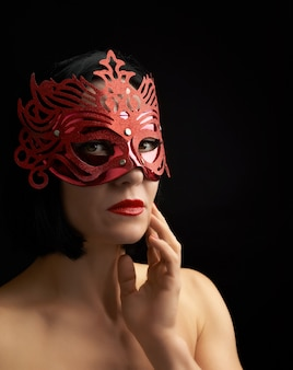 Beautiful adult woman of caucasian appearance with black hair wearing a red shiny carnival mask