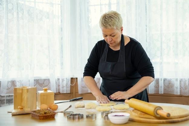 自家製ピタパンエンパナーダを調理する美しい大人の女性