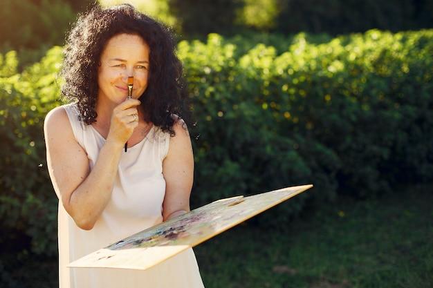 아름 다운 성인 여자 여름 필드에서 그리기