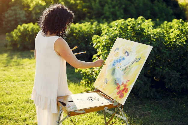 Beautiful adult woman drawing in a summer field