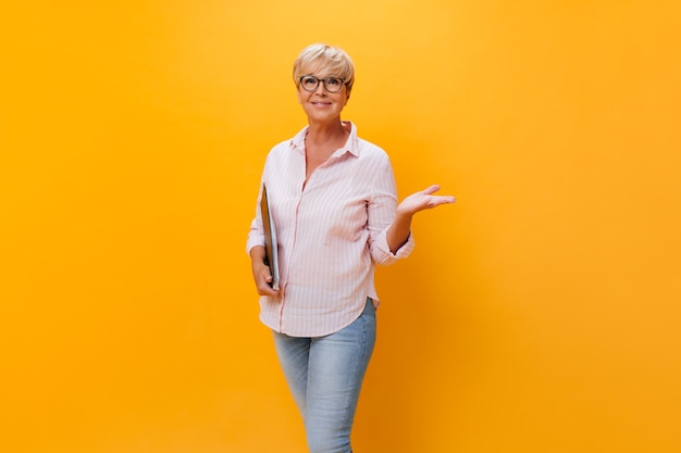 Beautiful adult woman in eyeglasses posing with paper sheets