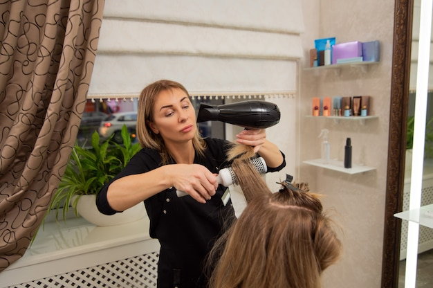 Beautiful adult woman hairdresser making a hairstyle to blonde customer using a hair dryer and round brush.