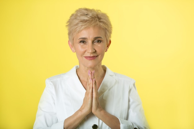 Красивая взрослая женщина в куртке на желтом фоне