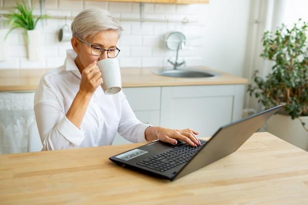Красивая взрослая женщина в очках за столом с ноутбуком дома с кружкой