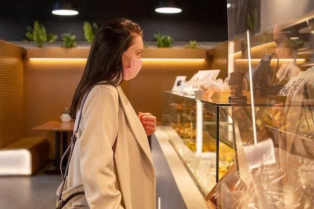 Красивая взрослая женщина в медицинской маске заказывает еду и напитки в кафе