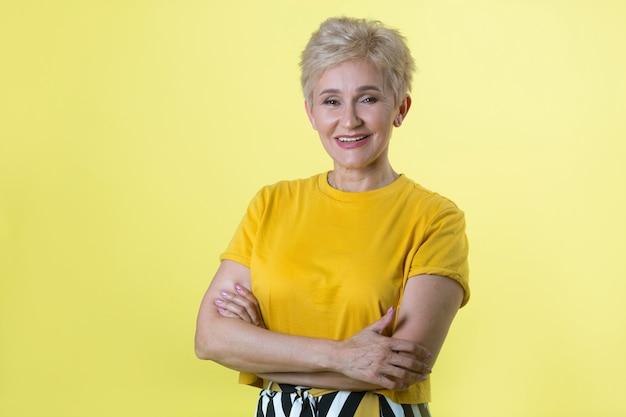 Красивая взрослая женщина в футболке на желтом фоне
