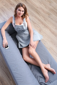 Beautiful adult woman lying in the couch