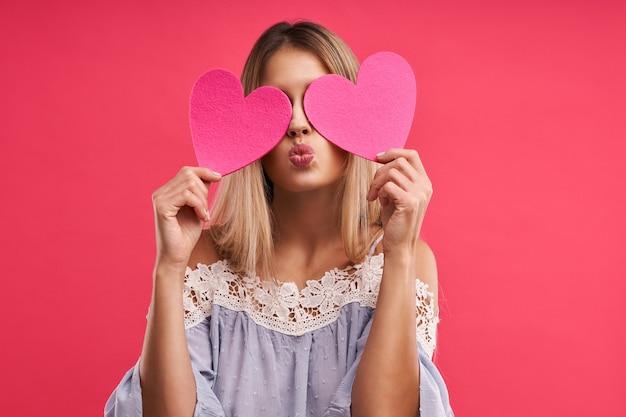 心でピンクでポーズをとる美しい大人の女性