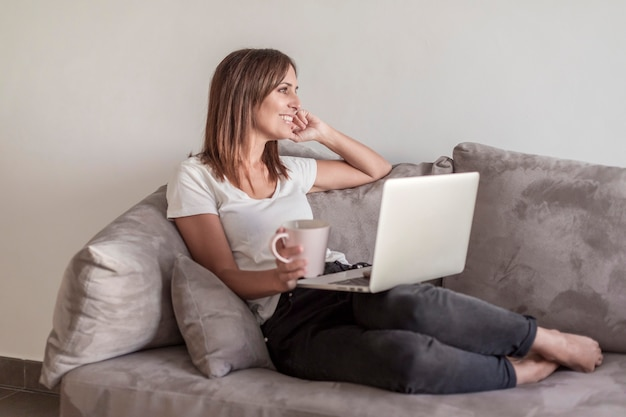 Beautiful adult woman relaxing on the sofa holding a cup of coffee while using laptop