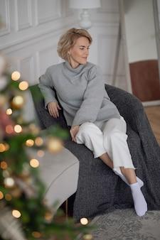 크리스마스 트리 근처 소파에 앉아 있는 아름다운 성인 여성