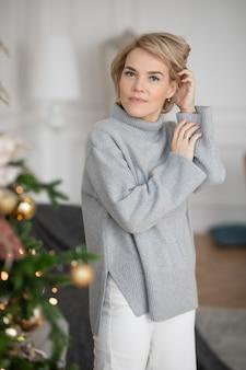 아름 다운 성인 여자는 크리스마스 트리 근처에 서