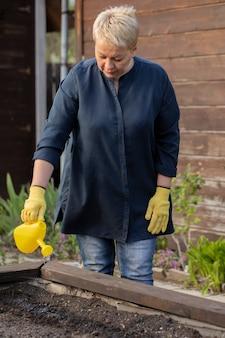 裏庭の彼女の庭に植えられた種子が付いている土に水をまく美しい大人の女性