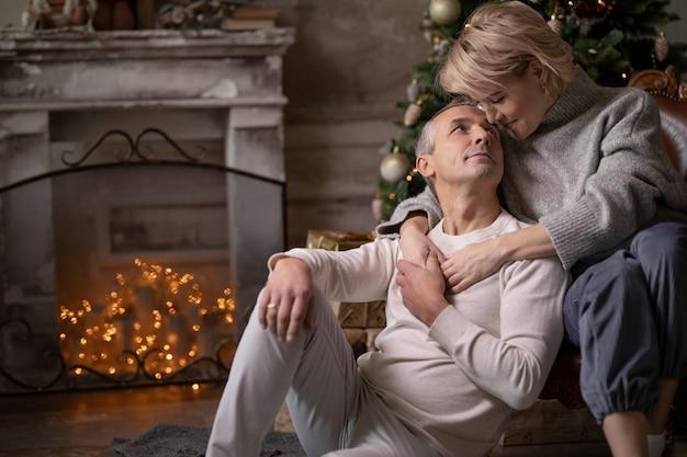 Красивая взрослая женщина с мужчиной сидят в кресле и обнимаются возле елки и камина