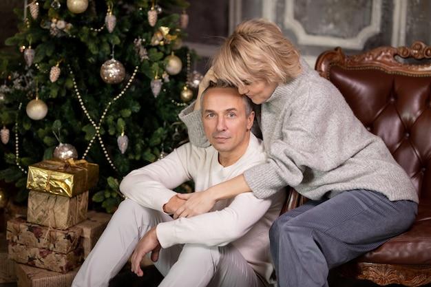 Красивая взрослая женщина с мужчиной сидят в кресле и обнимаются возле елки