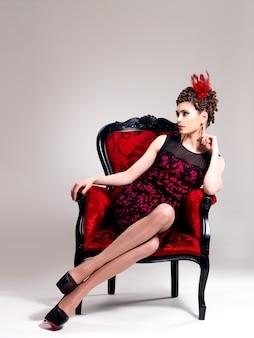ファッションの髪型とスタジオで赤いアームチェアのポーズを持つ美しい大人の女性