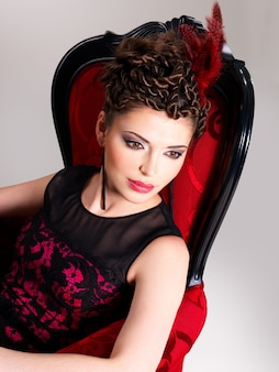 Beautiful adult woman with fashion hairstyle and red armchair poses at studio