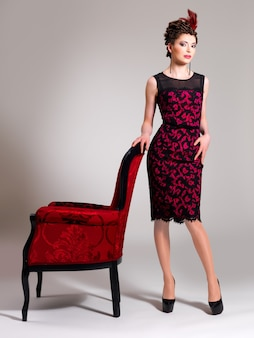Bella donna adulta con acconciatura di moda e poltrona rossa pone in studio