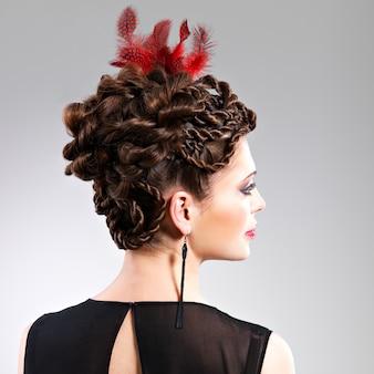 Bella donna adulta con acconciatura di moda con piuma rossa nei capelli