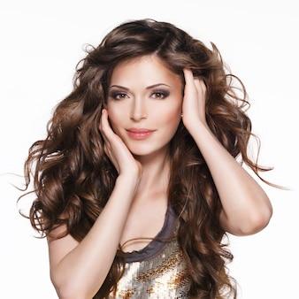 긴 갈색 곱슬 머리를 가진 아름 다운 성인 여자입니다. 흰색 배경 위에 패션 모델