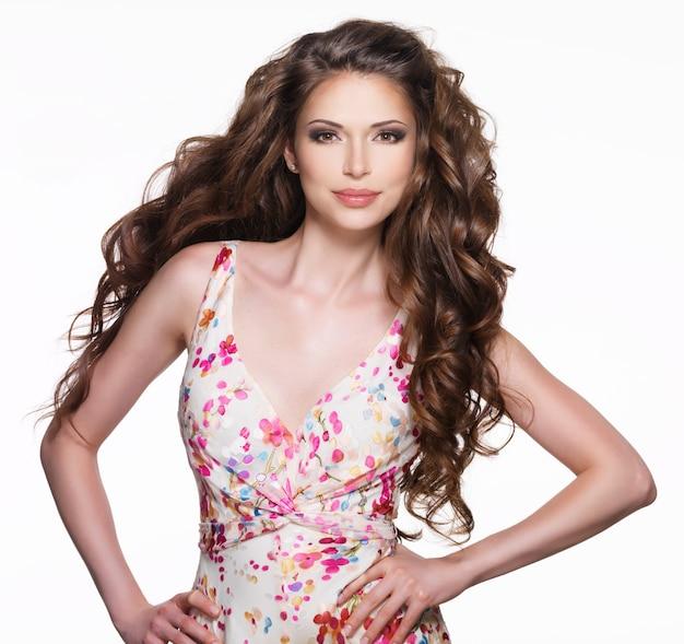 Красивая взрослая женщина с длинными каштановыми вьющимися волосами. модель на белом фоне