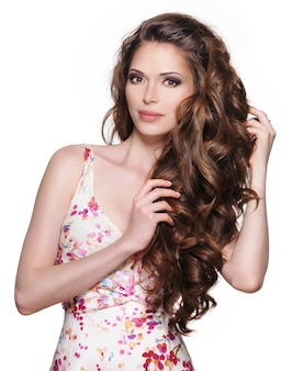 長い茶色の巻き毛を持つ美しい大人の女性。白い背景の上のファッションモデル