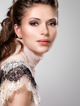 茶色の長い巻き毛を持つ美しい大人の女性。スタジオでポーズのファッションモデル