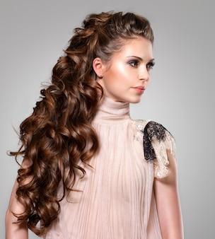 Bella donna adulta con capelli ricci marroni lunghi. modello di moda che propone allo studio