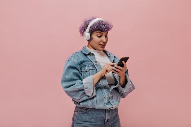 特大のジャケットとジーンズで短い髪の美しい大人の女性はsmsを書きます。ピンクの電話でポーズをとる白いヘッドフォンの女性。