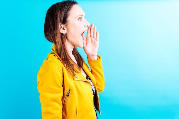 Красивая взрослая молодая женщина в летнем платье бабочки и желтой куртке на синем фоне громко разговаривает с рукой на рту. концепция говорить громко или кричать