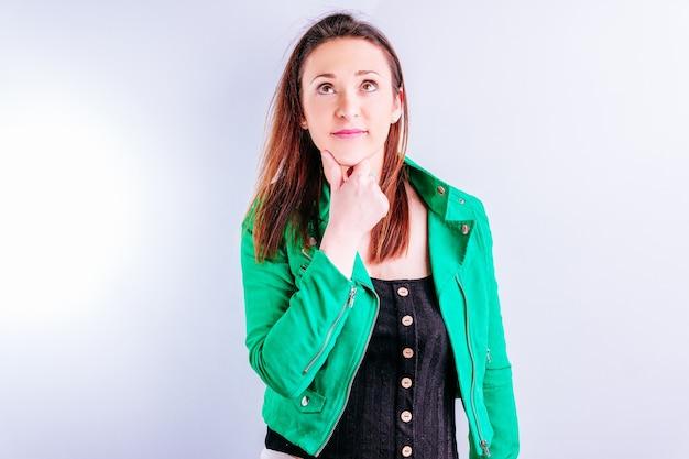 Красивая взрослая молодая женщина в зеленой куртке с рукой на задумчивом лице с белым фоном с copyspace