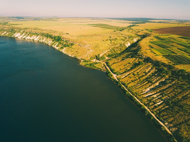 Beautiful aerial drone landspace of river or lake with amazing green hills during summer.
