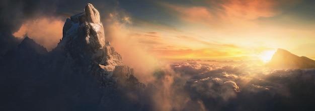 Красивый воздушный пейзаж горной вершины на закате над облаками - панорамный