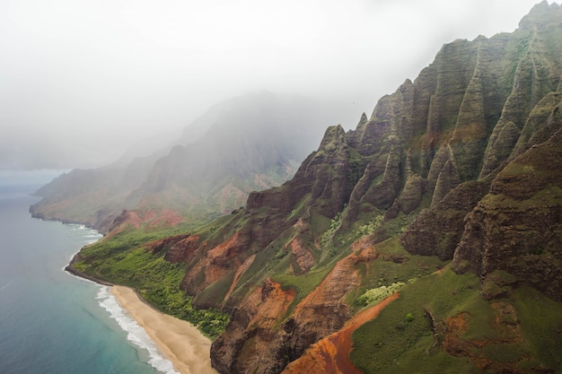 Beautiful aerial shot of the coast of napali with clear beautiful water and steep rocks