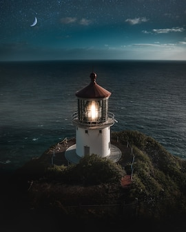 Beautiful aerial shot of a lit lighthouse on a green hill with the half-moon in the night sky