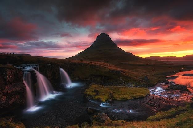 日没時の丘に囲まれた滝の美しい空中ショット