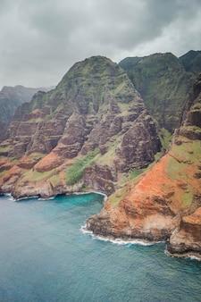澄んだ美しい水と急な岩でナパリ海岸の美しい空中ショット