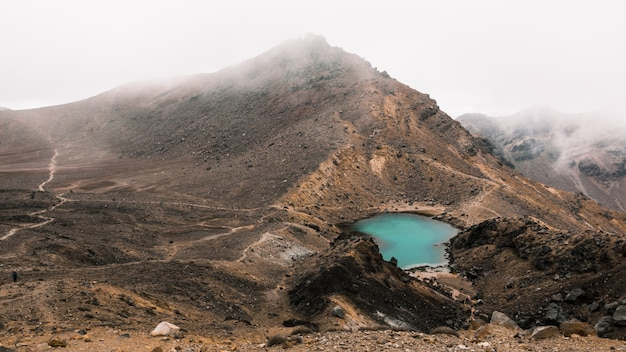 Beautiful aerial shot of a small lake in the middle of the desert near a mountain on a foggy day