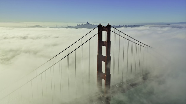 Beautiful aerial shot of the top of a bridge surrounded by clouds and blue sky