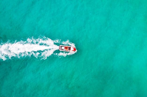 Красивый водный мотоцикл с высоты птичьего полета в море. развлечения на водных мотоциклах в морской бирюзовой воде. туристы развлекаются на отдыхе. вид сверху с воздуха. люди играют на водных лыжах. удивительный фон природы