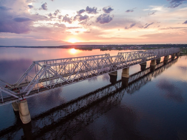 Beautiful aerial view of the railway bridge across the volga river at sunset. it connects two banks via the river volga