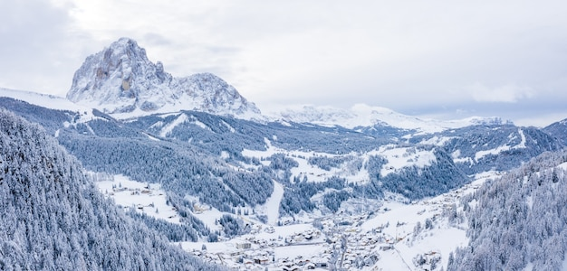 Beautiful aerial view of a ski resort and a village in a mountains landscape, in the alps