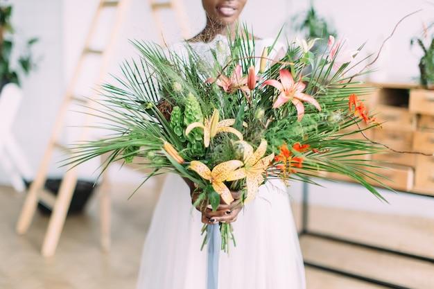 スタジオでトロピカルブーケを持つ美しいアフリカ系アメリカ人の花嫁