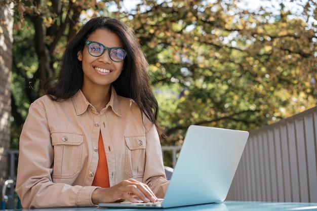 아름 다운 아프리카 계 미국인 사업가 노트북을 사용 하여 입력, 카메라를 찾고. 성공적인 비즈니스 개념