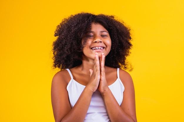 희망과 제발 개념을 표현하는 기도 제스처에 함께 손을 가진 아름다운 아프리카계 미국인 아이. 곱슬 머리를 가진 브라질 소녀입니다.