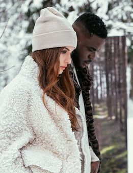 The beautiful african-american couple and a girl of european appearance in a winter forest against the background of summer in stylish clothes. the concept of summer in winter.