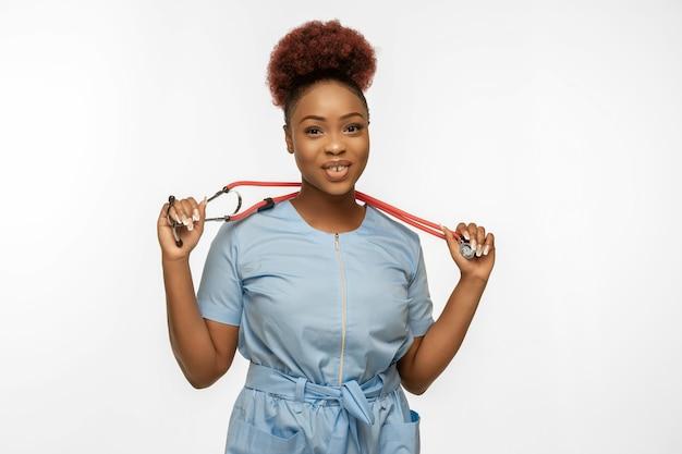白いスタジオの背景に美しいアフリカ系アメリカ人の医者