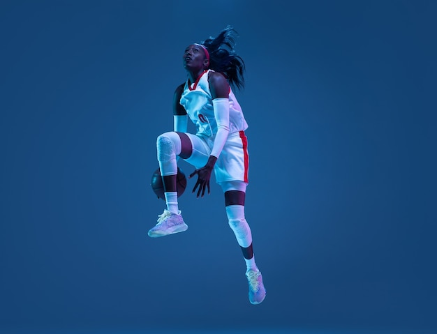 Beautiful african american female basketball player in motion and action in neon light on blue wall concept of healthy lifestyle professional sport hobby